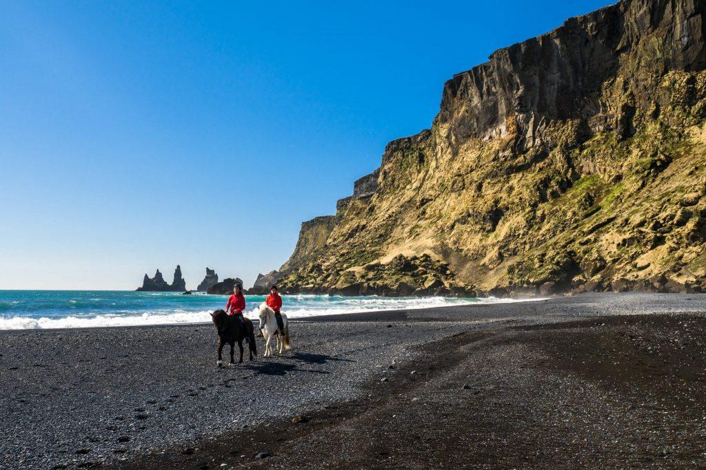 Horse riding on a black sand beach